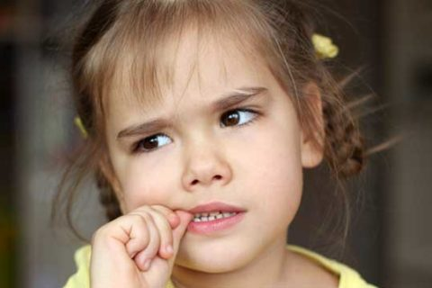 Little girl biting her nails
