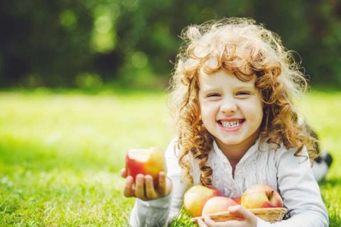 Little girl eating apple and showing her white teeth's