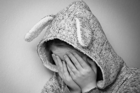Girl hiding her face with hand